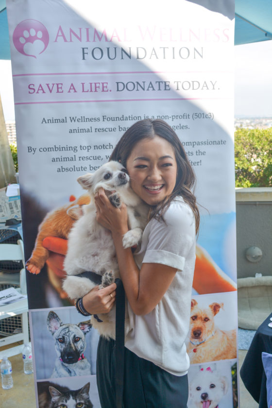 Amy Okuda takes a minute to play with dogs available for adoption at LA-based Animal Awareness animal rescue